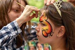 NOVOSIBIRSK ROSJA, CZERWIEC, - 26, 2016: Mistrz rysuje farba wzory na dziewczyny twarzy w miasto parku Fotografia Stock
