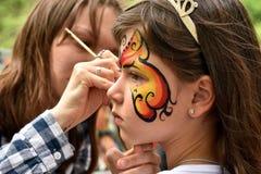 NOVOSIBIRSK ROSJA, CZERWIEC, - 26, 2016: Mistrz rysuje farba wzory na dziewczyny twarzy w miasto parku Fotografia Royalty Free