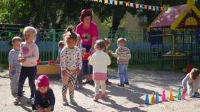 NOVOSIBIRSK, RUSIA - 16 de agosto de 2017: En guardería, la mujer que juega con los niños, juegos activos al aire libre almacen de video