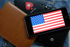 NOVOSIBIRSK, RUSIA - 13 DE DICIEMBRE DE 2016: La bandera de América en el iphone Apple y el logotipo Pokerstars Foto de archivo