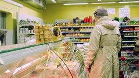 NOVOSIBIRSK, RUSIA, el 14 de abril de 2015, mujer madura elige productos de carne en colmado 3840x2160 metrajes