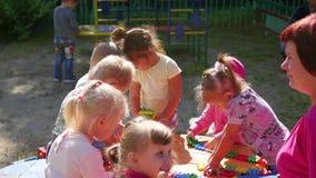 NOVOSIBIRSK, RUSLAND - Augustus 16, 2017: In kleuterschool, de vrouw die met de kinderen, actieve spelen in openlucht spelen stock video