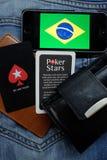 NOVOSIBIRSK, RUSLAND - DECEMBER 13, 2016: De vlag van Brazilië en embleem Pokerstars op jeansachtergrond Royalty-vrije Stock Foto's