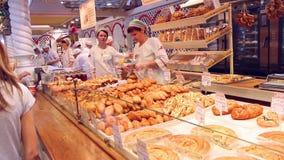 NOVOSIBIRSK, RUSLAND - Juni 27, 2016: de mensen kopen bakkerijproducten bij de markt stock videobeelden