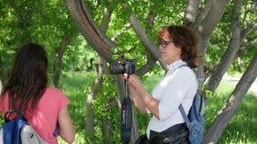 NOVOSIBIRSK, RUSLAND - Juni 5, 2017: vrouwelijke fotograaf die een meisje op camera fotograferen stock video