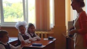 Novosibirsk, Rusland - september, 1, 2015 De eerstegraadsstudenten en de leraar zijn in schoolklaslokaal bij eerste les E stock footage