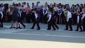 Novosibirsk, Rusland 1 September, 2015 De schoollijn is in schoolplein met leerlingen en leraren De kinderen keren terug aan stock video