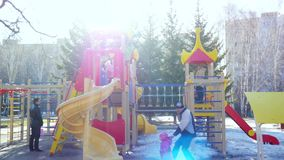 NOVOSIBIRSK, RUSSIA, 14 APRIL 2015, Playground, Children playing in playground in winter on the sun background stock video