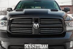 Black Dodge Ram with an engine of 5.7 liters front radiator grille, hood and headlight view on the car parking with snow. Novosibirsk, Russia - 12.01.2018: Black royalty free stock photo