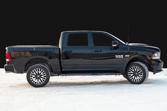 Black Dodge Ram with an engine of 5.7 liters side view on the background of black wall. Novosibirsk, Russia - 12.01.2018: Black Dodge Ram with an engine of 5.7 royalty free stock image