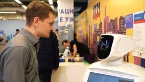 Novosibirsk, Russia - 21 febbraio 2018: L'uomo comunica con un robot e una risata video d archivio