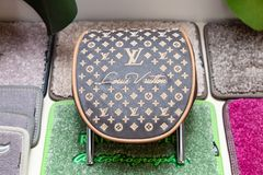 Handmade brown and beige leather headrest louis vuitton for a car in a vehicle interior design workshop against the background of stock images
