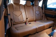 The interior of the car with a view of the rear seats and doors with light brown leather trim stock photo