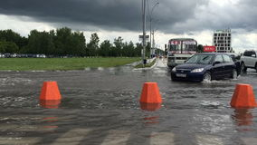 Novosibirsk, Russia, July 3, 2016. Flooded road after heavy rains,cars moving slowly in deep waters stock footage