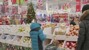 NOVOSIBIRSK,RUSSIA - November 25,2017: Christmas sale of toys and Christmas trees until Christmas. People in the. Christmas gifts for loved ones. Christmas sale stock footage