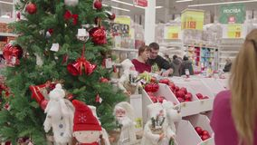 NOVOSIBIRSK,RUSSIA - November 25,2017: Christmas sale of toys and Christmas trees until Christmas. People in the. Christmas gifts for loved ones. Christmas sale stock video