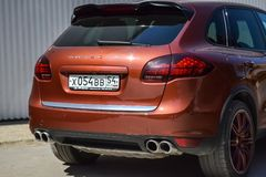 Rear side view of Porsche Cayenne 958 2013 in brown color after cleaning before sale in a sunny summer day with gray wall on. Novosibirsk, Russia - 05.29.2019 stock photography