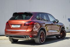 Rear view of Porsche Cayenne 958 2013 in brown color after cleaning before sale in a sunny summer day with gray wall on background. Novosibirsk, Russia - 05.29 royalty free stock images