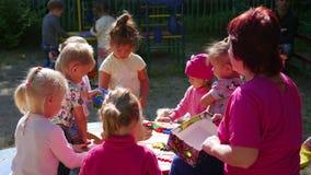 NOVOSIBIRSK RYSSLAND - Augusti 16, 2017: I dagis kvinnan som spelar med barnen, aktiva lekar utomhus lager videofilmer
