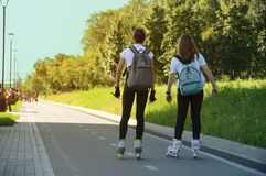 Novosibirsk 07-31-2018. Two young girls go roller-skating in park. royalty free stock image