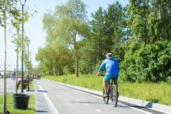 Novosibirsk 07-31-2018 Um homem está montando uma bicicleta no parque imagens de stock