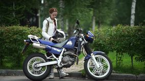 Novosibirsk 2016: Woman with two pigtails standing near a motorcycle stock video footage