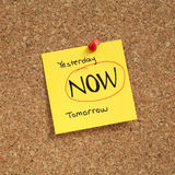 NOW. Adhesive note pinned on cork bulletin board with 'Yesterday NOW tomorrow' text Stock Photos