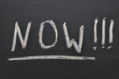 Now concept. Word Now handwritten on black chalkboard Royalty Free Stock Images