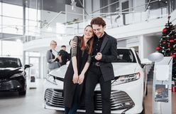 Now her dream comes true. Car salesman giving the key of the new car to the young attractive owners.  Royalty Free Stock Photo