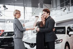 Now her dream comes true. Car salesman giving the key of the new car to the young attractive owners.  Stock Photos
