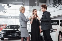 Now her dream comes true. Car salesman giving the key of the new car to the young attractive owners.  Royalty Free Stock Image