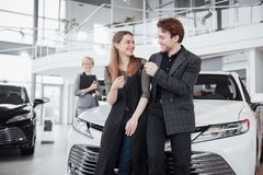Now her dream comes true. Car salesman giving the key of the new car to the young attractive owners.  Royalty Free Stock Photography