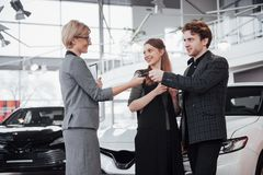 Now her dream comes true. Car salesman giving the key of the new car to the young attractive owners.  Stock Photo