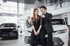 Now her dream comes true. Car salesman giving the key of the new car to the young attractive owners.  Stock Image