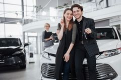 Now her dream comes true. Two happy young attractive owners of car, elegant salesperson at background.  Royalty Free Stock Photos