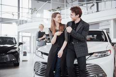 Now her dream comes true. Two happy young attractive owners of car, elegant salesperson at background.  Stock Photo
