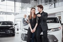 Now her dream comes true. Two happy young attractive owners of car, elegant salesperson at background.  Stock Image