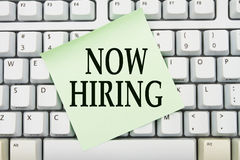 Now Hiring. Applying for jobs online, Computer keyboard keys with sticky note with words Now Hiring Royalty Free Stock Images