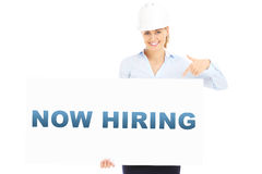 Now hiring banner. A picture of a pretty woman in a hard hat showing a banner with now hiring inscription Royalty Free Stock Photos