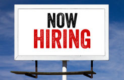 Now Hiring Billboard. Sign against Blue Sky Background royalty free stock image