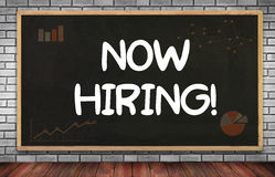 NOW HIRING!. On brick wall and chalkboard background Stock Photo