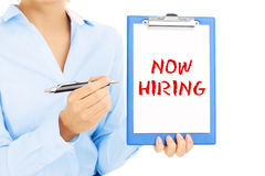 Now hiring. Businesswoman with now hiring sign pointing by pen Stock Images