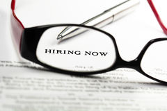 Now Hiring. Classified ad through reading glasses Stock Photos