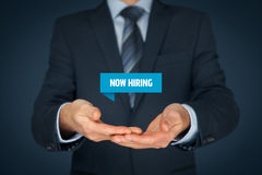 Now hiring. Human resources concept. Businessman (recruiter, HR staffer) hold virtual label with text stock photography
