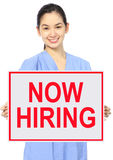 Now Hiring. A medical person holding a recruitment sign Royalty Free Stock Images