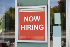 Now hiring sign outside modern office building. Closeup of now hiring sign outside modern office building royalty free stock image
