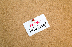 Now Hiring Sticky Note Concept. Sticky Note On Cork Board Background Now Hiring concept Stock Photo