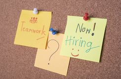 Now hiring text on sticky note or post is on cork bulletin. Billboard Royalty Free Stock Photo