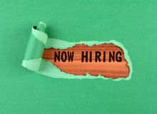 Now hiring word. The text Now hiring appearing behind ripped green paper on wood Stock Image