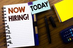 Now hiring Written on Sticky Note Message. Wooden background Stock Image